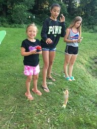 Three kids with a big fish caught out of our fishing pond at Camp Chautauqua